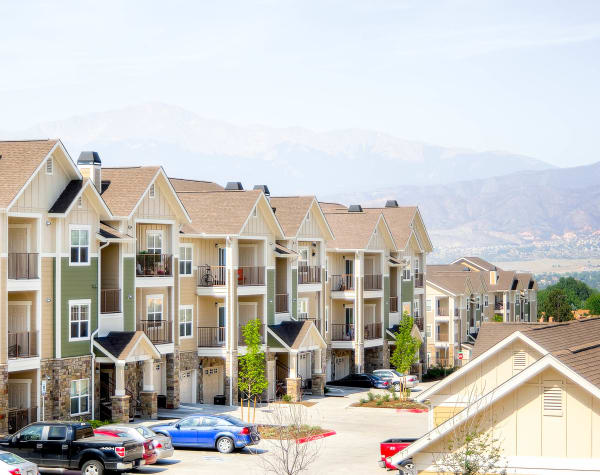 Apartment buildings and mountains view at Peaks at Woodmen Apartments in Colorado Springs, Colorado