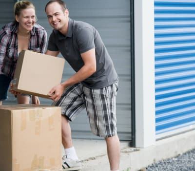 Couple with boxes near self storage units at A++ Secure Storage