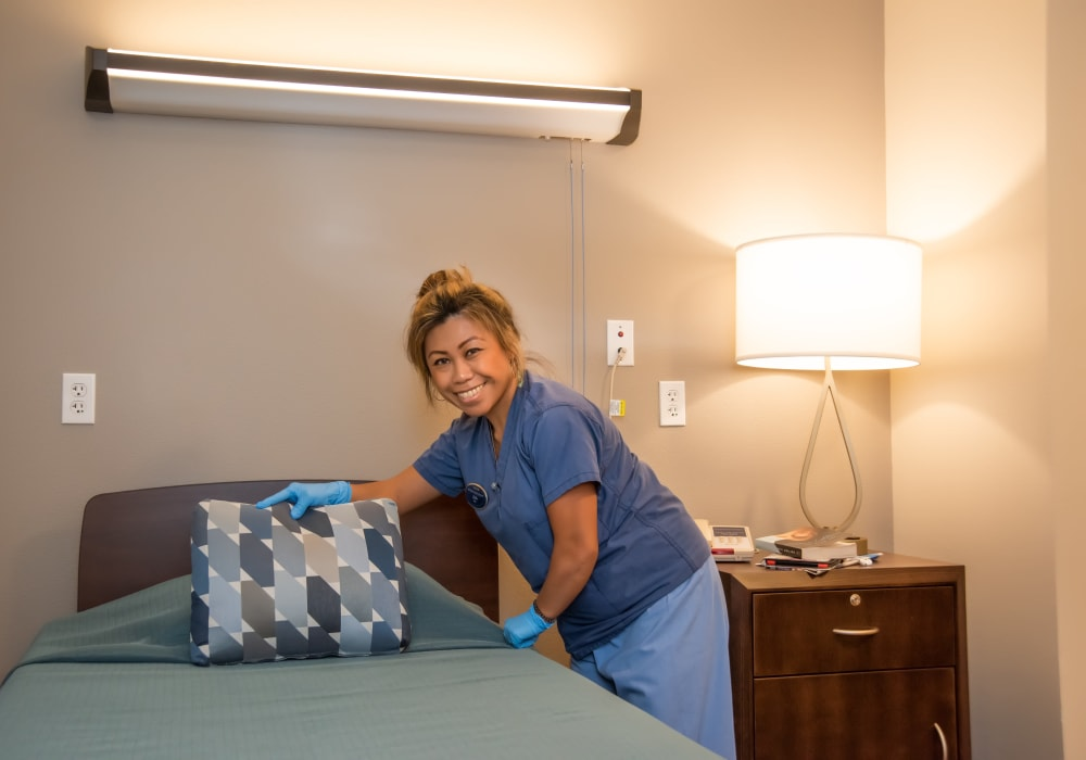 A staff member making a bed at Mission Healthcare at Bellevue in Bellevue, Washington.