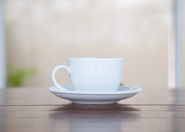 A white cup and saucer on a wooden table by the window at a Radiant Senior Living