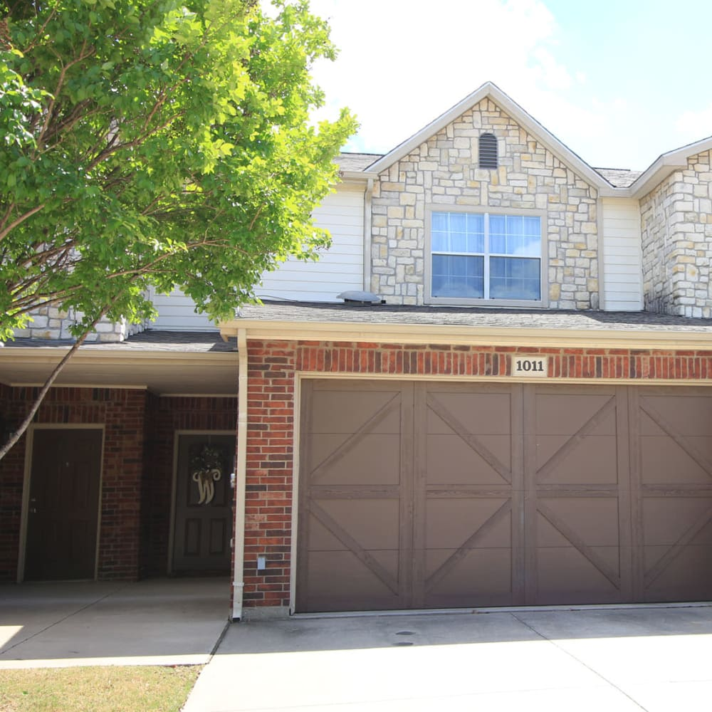 Mature tree and a private garage outside the entrance to a townhome at Oaks Estates of Coppell in Coppell, Texas