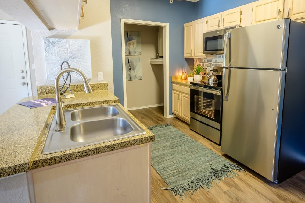 Stainless-steel appliances and granite countertops in a model home's kitchen at 23Hundred @ Ridgeview in Plano, Texas