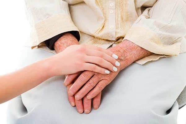 Woman holding hand of senior woman at The Retreat at Camden in Camden, South Carolina