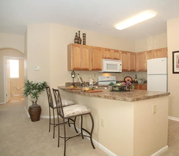 Modern kitchen and breakfast bar in model senior apartment at Burr Ridge Senior Living in Burr Ridge, IL