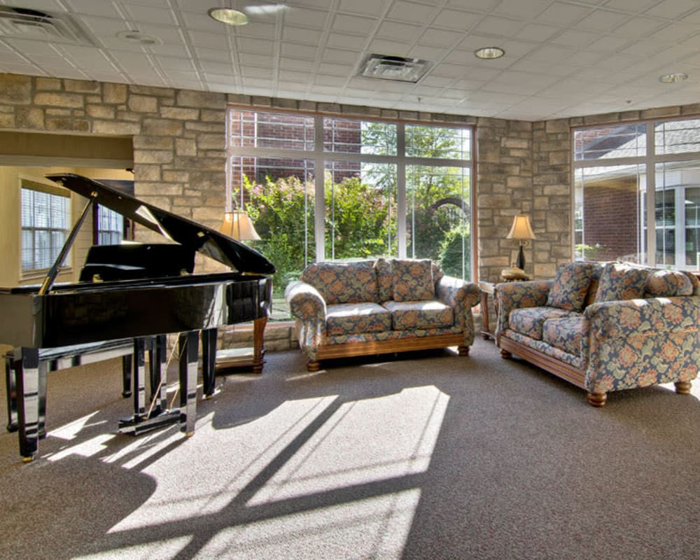 A piano and seating in the lobby at The Neighborhoods at Quail Creek in Springfield, Missouri