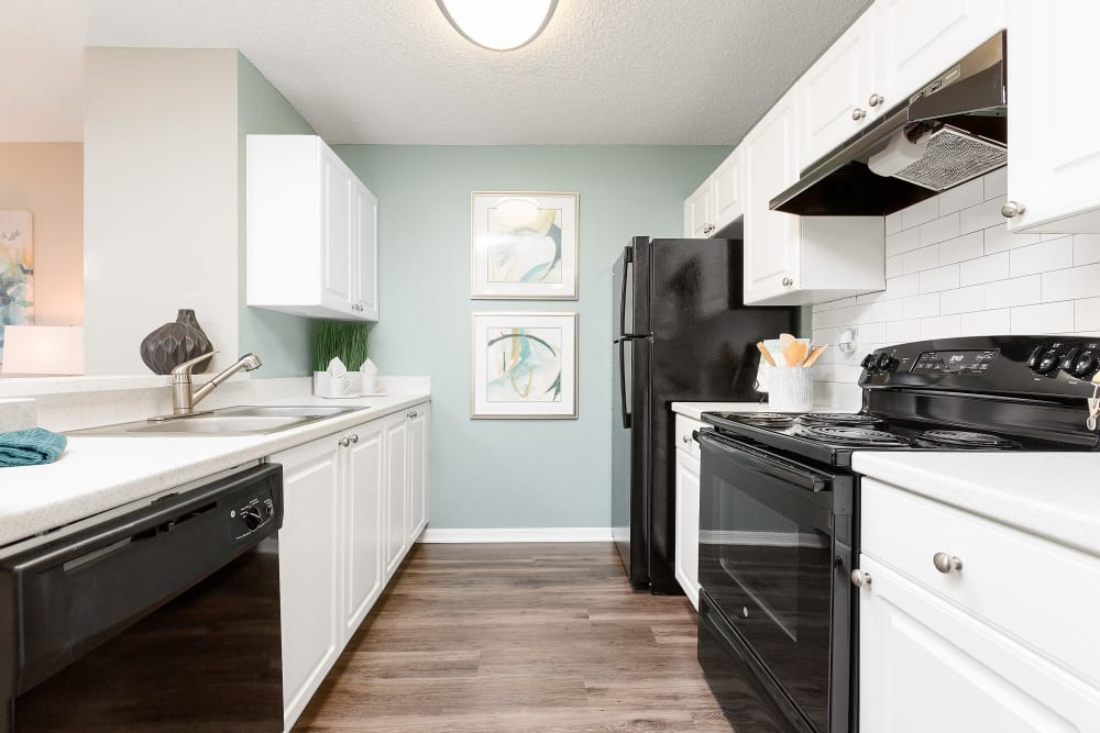 Kitchen with wood style flooring and black appliances at The Avenue in Ocoee, Florida