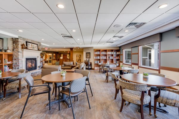 Bistro lounge with round tables, couches, fireplace and books at Arbor Glen Senior Living in Lake Elmo, Minnesota