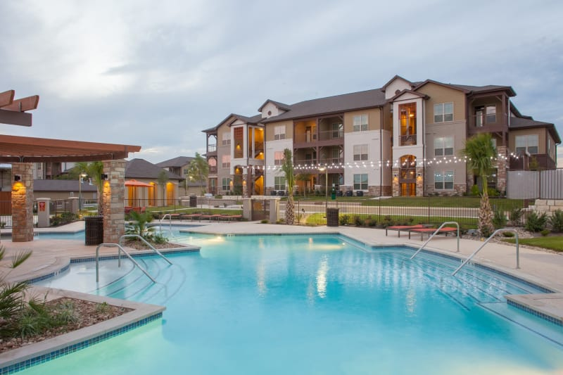 Outdoor pool with gazebo and lounge chairs at Firewheel Apartments in San Antonio