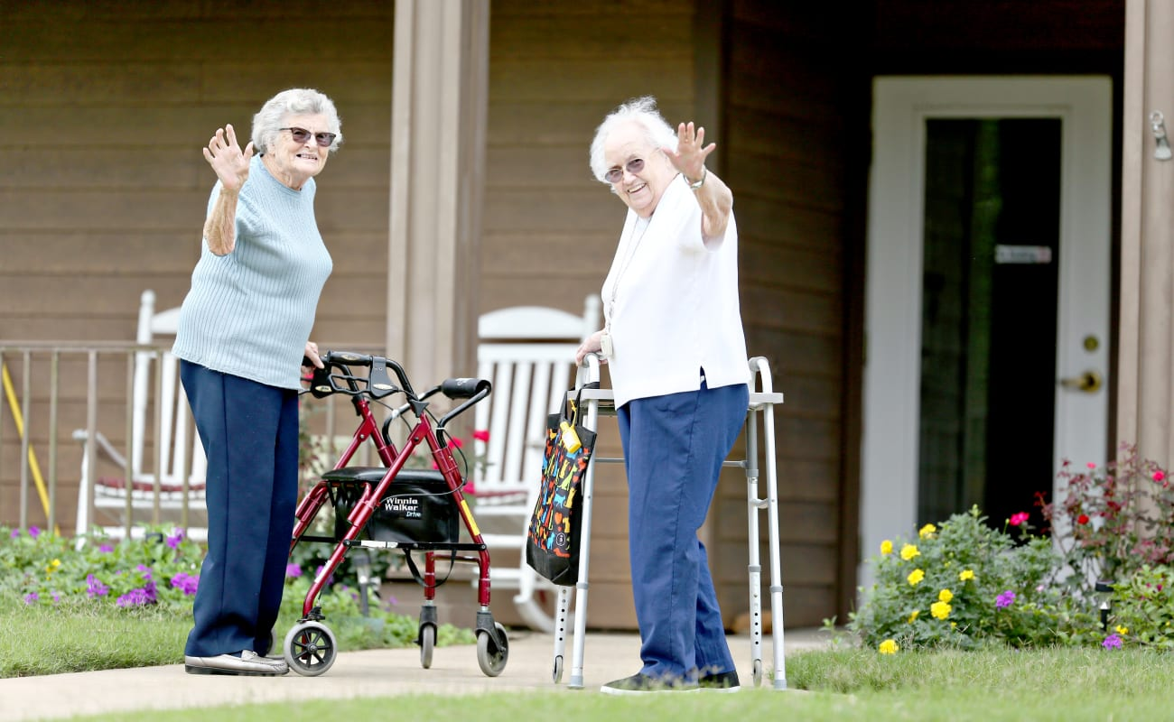 Two resident friends waving hello on their walk at Providence Assisted Living in Searcy, Arkansas.