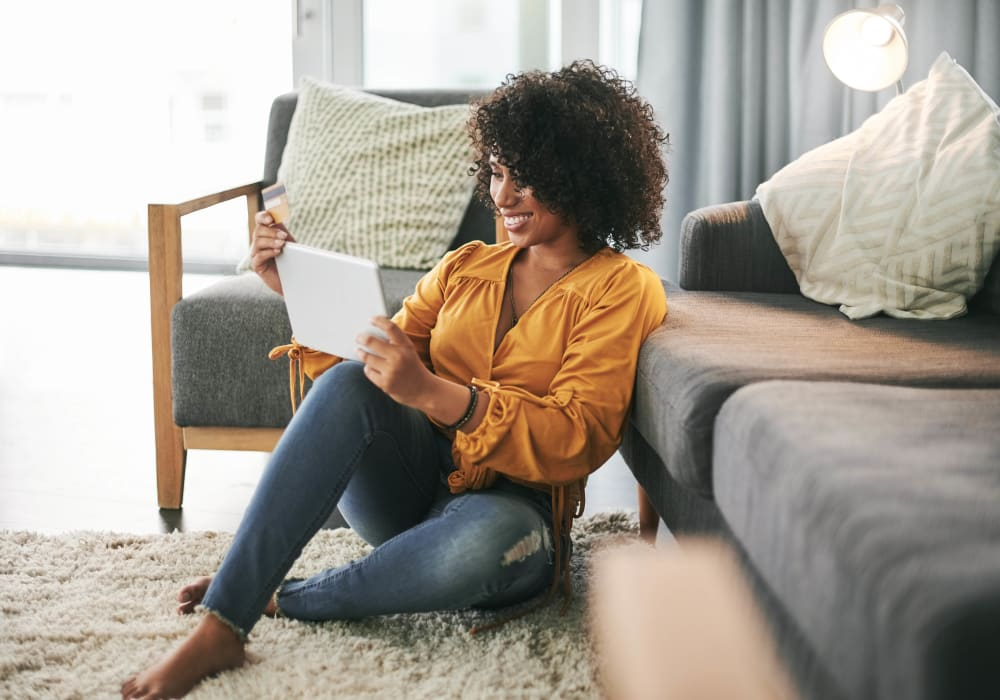 Woman enjoying her living room at Dunbarton Apartments in Georgetown, Delaware