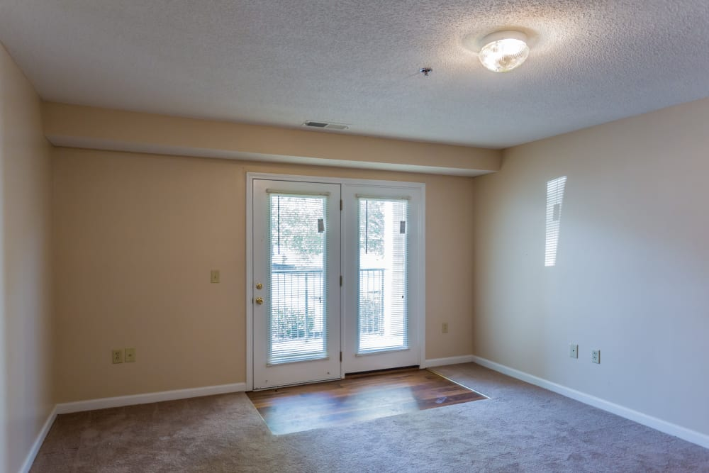 A living room with doors to the patio at Park Ridge Apartments in Jackson, Tennessee