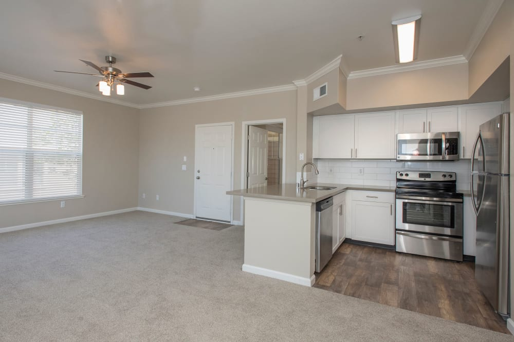 Living room with ceiling fan and beautiful kitchen at The Vintage at South Meadows Condominium Rentals in Reno, Nevada