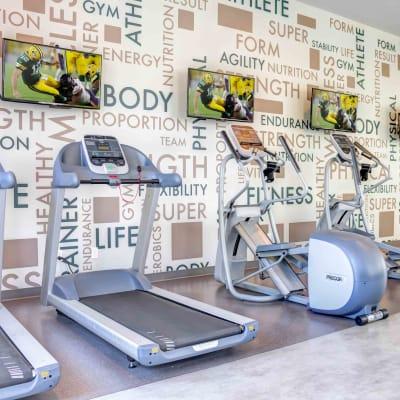 Cardio machines with individual flatscreen TVs in the onsite fitness center at Sofi Berryessa in San Jose, California
