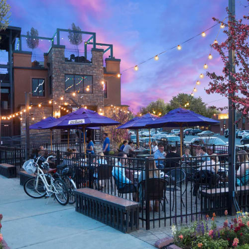 People eating outside in enclosed, umbrella covered area at sunset at Marq Midtown 205 in Charlotte, North Carolina