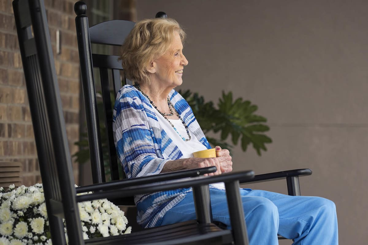 A resident enjoying her coffee outside at The Oxford Grand Assisted Living & Memory Care in Kansas City, Missouri