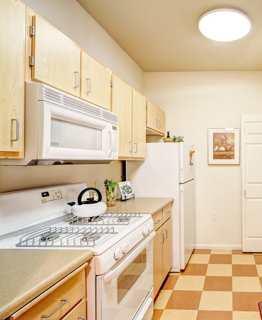 Beautiful white appliances with a stainless-steal sink at Laguna Creek Apartments in Elk Grove, California