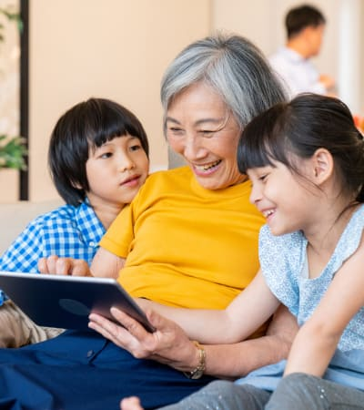 Resident sitting and reading a book with her grand-kids at Nikkei Manor in Seattle, Washington