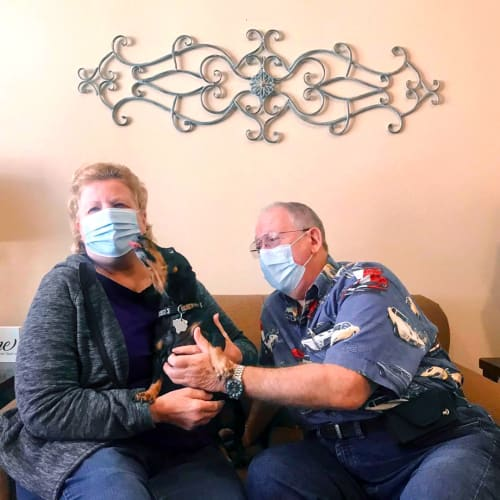 Masked residents sitting on a couch with their dog at Oxford Glen Memory Care at Carrollton in Carrollton, Texas
