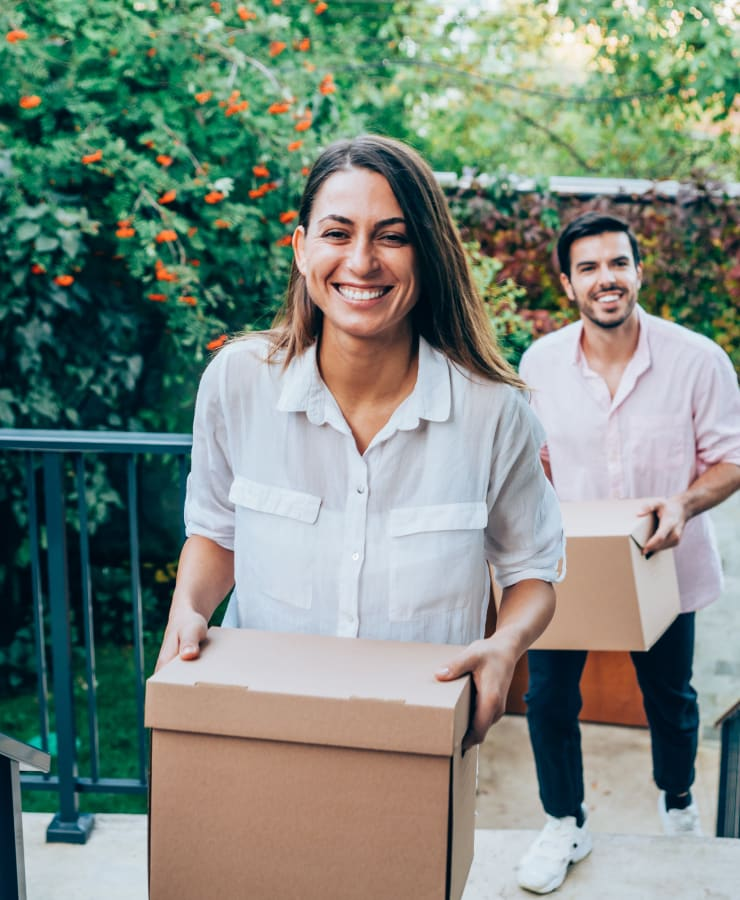 A smiling couple carrying items to store at Missouri Flat Storage Depot in Placerville, California