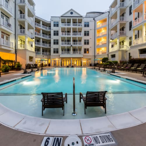Resort style pool surrounded by lounge chairs and building units of Marquis at Buckhead in Atlanta, Georgia
