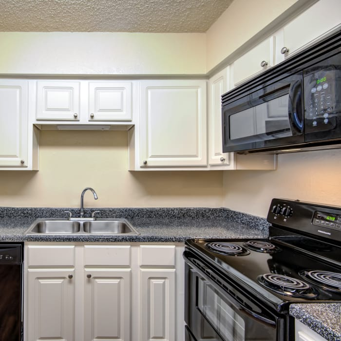 Modern kitchen with black appliances in model home at Grayson Ridge in North Richland Hills, Texas