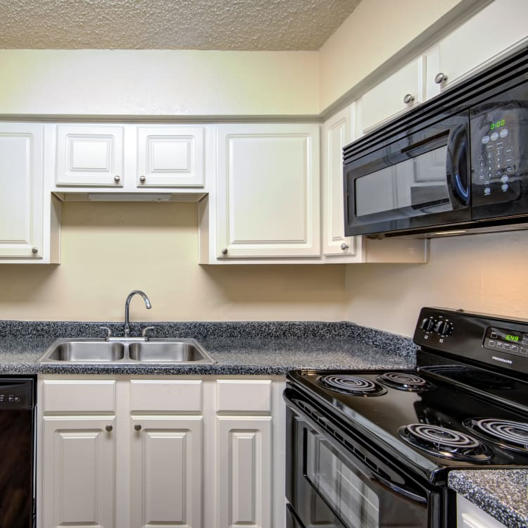 Gourmet kitchen with white cabinetry and granite countertops in a model home at Grayson Ridge in North Richland Hills, Texas