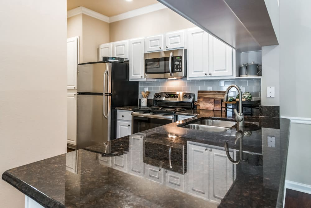 Bright kitchen with granite counters and stainless steel appliances at Marquis at Carmel Commons in Charlotte, North Carolina