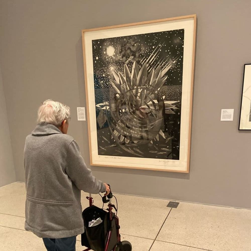 A resident looking at art at Inspired Living Tampa in Tampa, Florida.