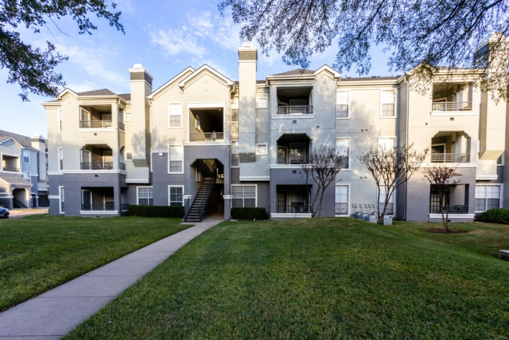 Unit entrance surrounded by green landscaping at Marquis at Stonegate in Fort Worth, Texas