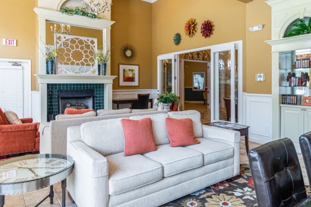 Community clubhouse sitting area with sofas and large fireplace at Marquis of Carmel Valley in Charlotte, North Carolina