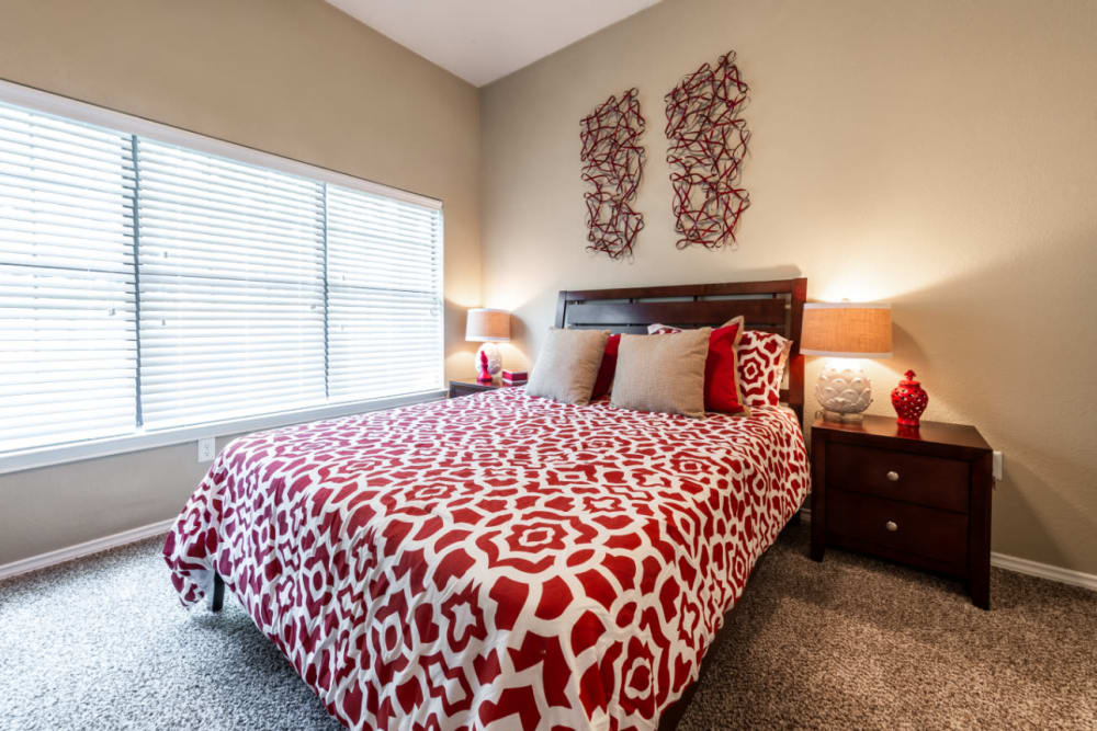 Bright and carpeted bedroom with multiple large windows at Marquis at Waterview in Richardson, Texas