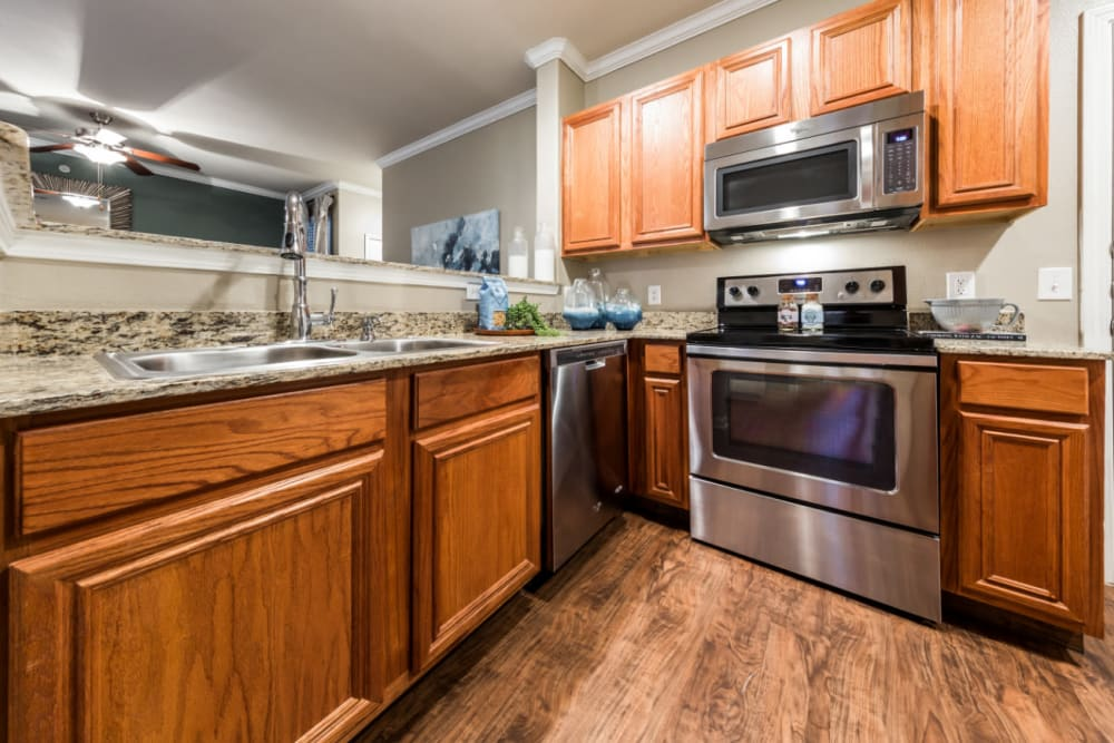 Modern style kitchen with stainless steel appliances and granite countertops at Marquis at The Cascades in Tyler, Texas