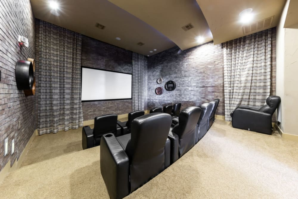 Community clubhouse theater with recliner chairs and large screen at Marquis at the Reserve in Katy, Texas