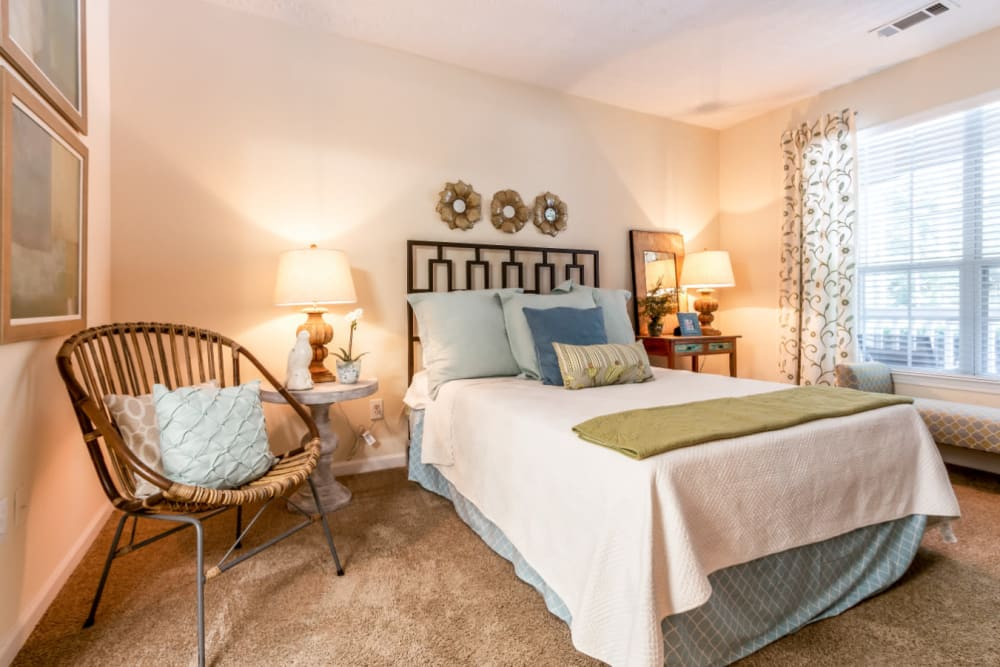 Spacious carpeted bedroom with large window at Marquis at Sugarloaf in Duluth, Georgia