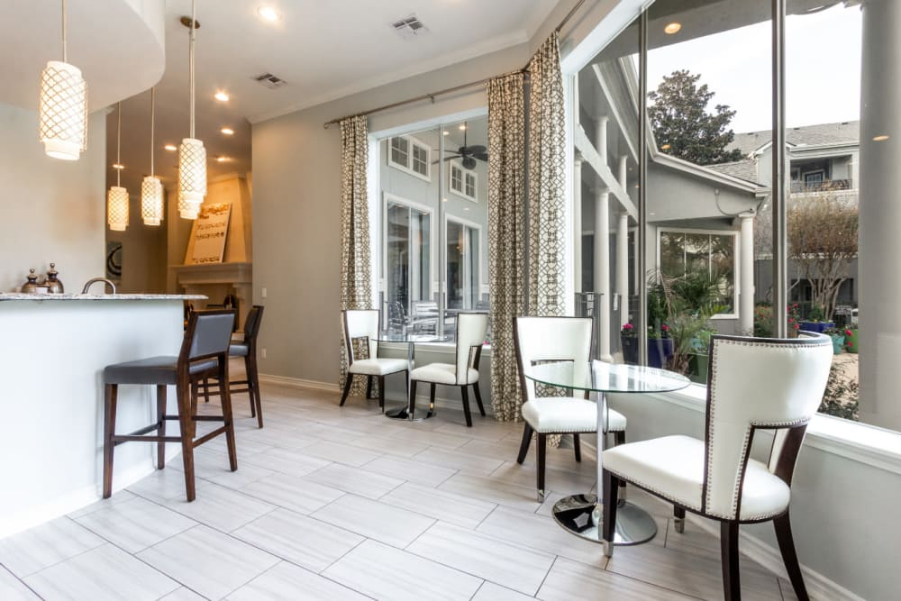 Community clubhouse kitchen and dining area with large windows at Marquis at Stonegate in Fort Worth, Texas