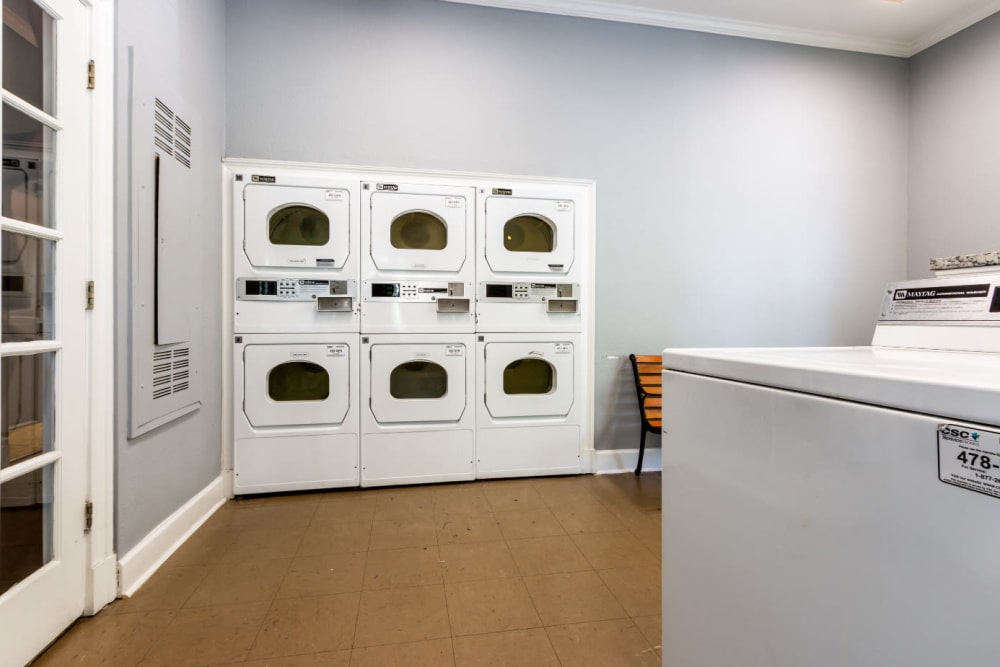 Coin operated dryer machines in community laundry room at Marquis at Sugarloaf in Duluth, Georgia