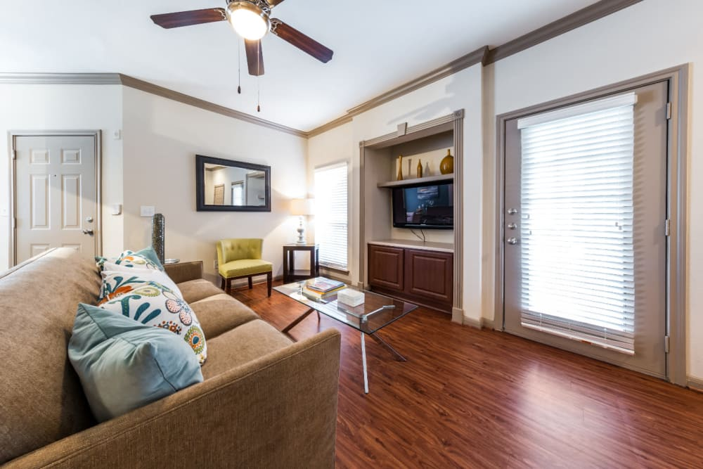Bright living room with built in entertainment center space and door to private balcony at Marquis on Park Row in Houston, Texas