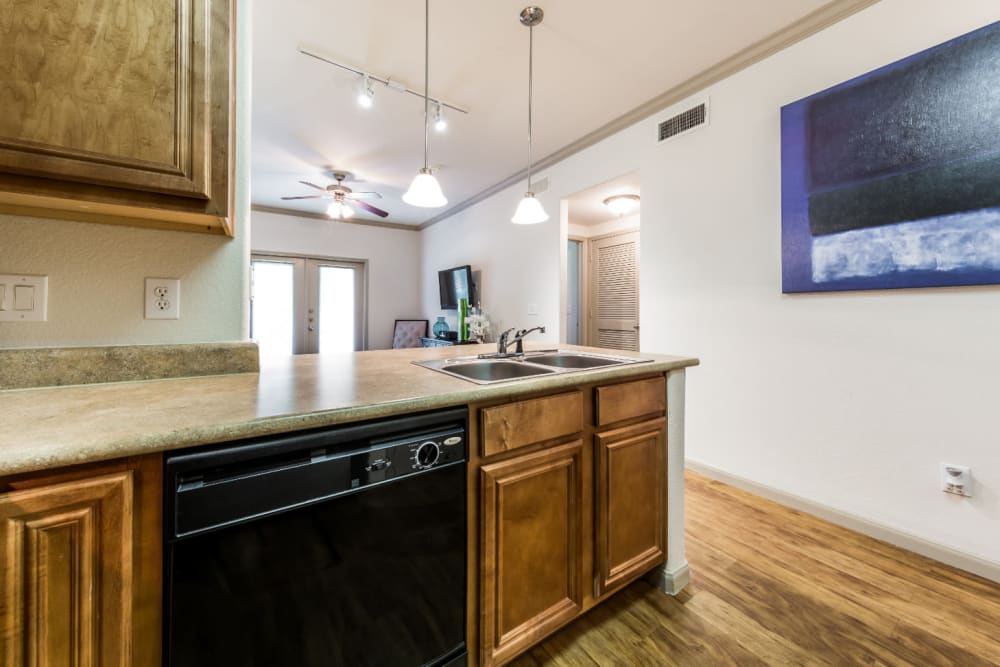 Bright kitchen with wood cabinets and flooring at Marquis at Clear Lake in Webster, Texas