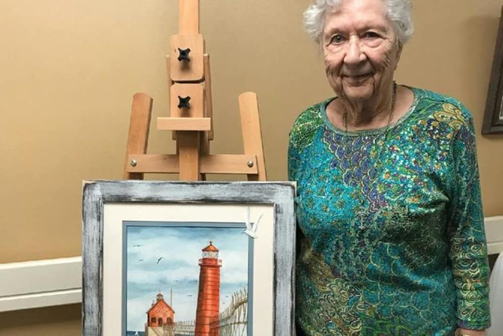 A resident with her painting of a lighthouse at Cumberland Pointe Health Campus in West Lafayette, Indiana