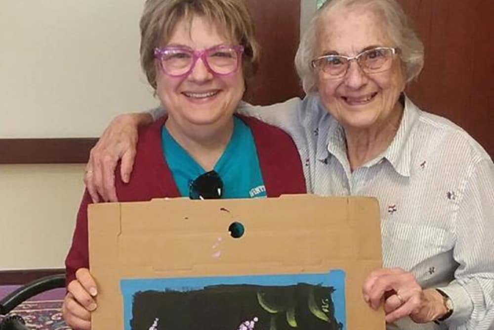 Two residents holding up a painting at Cumberland Pointe Health Campus in West Lafayette, Indiana