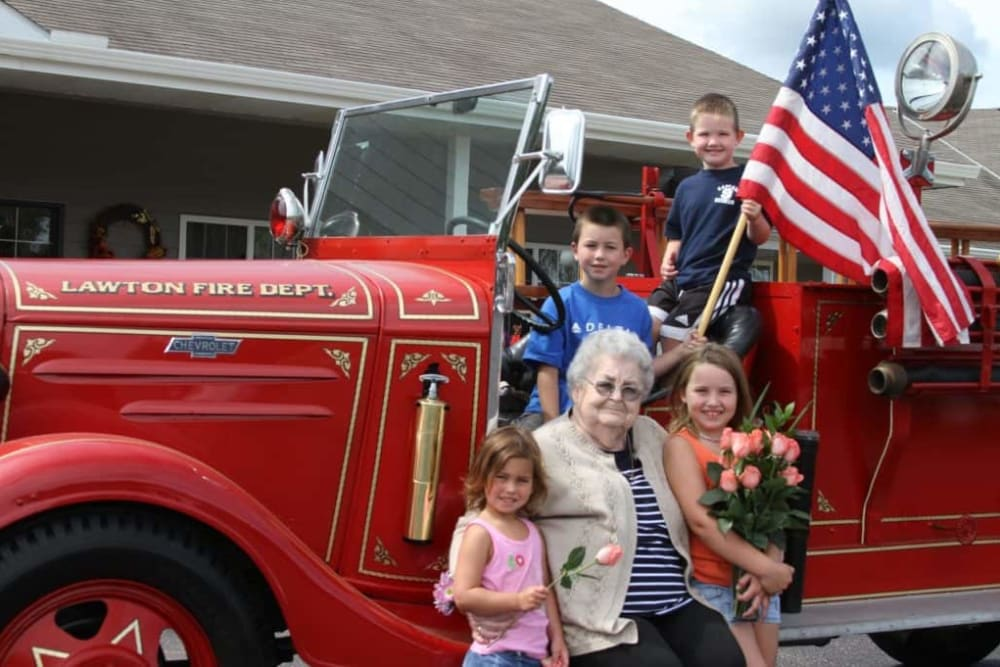 Resident and family pose with antique fire truck visiting Lawton Senior Living in Lawton, Iowa.