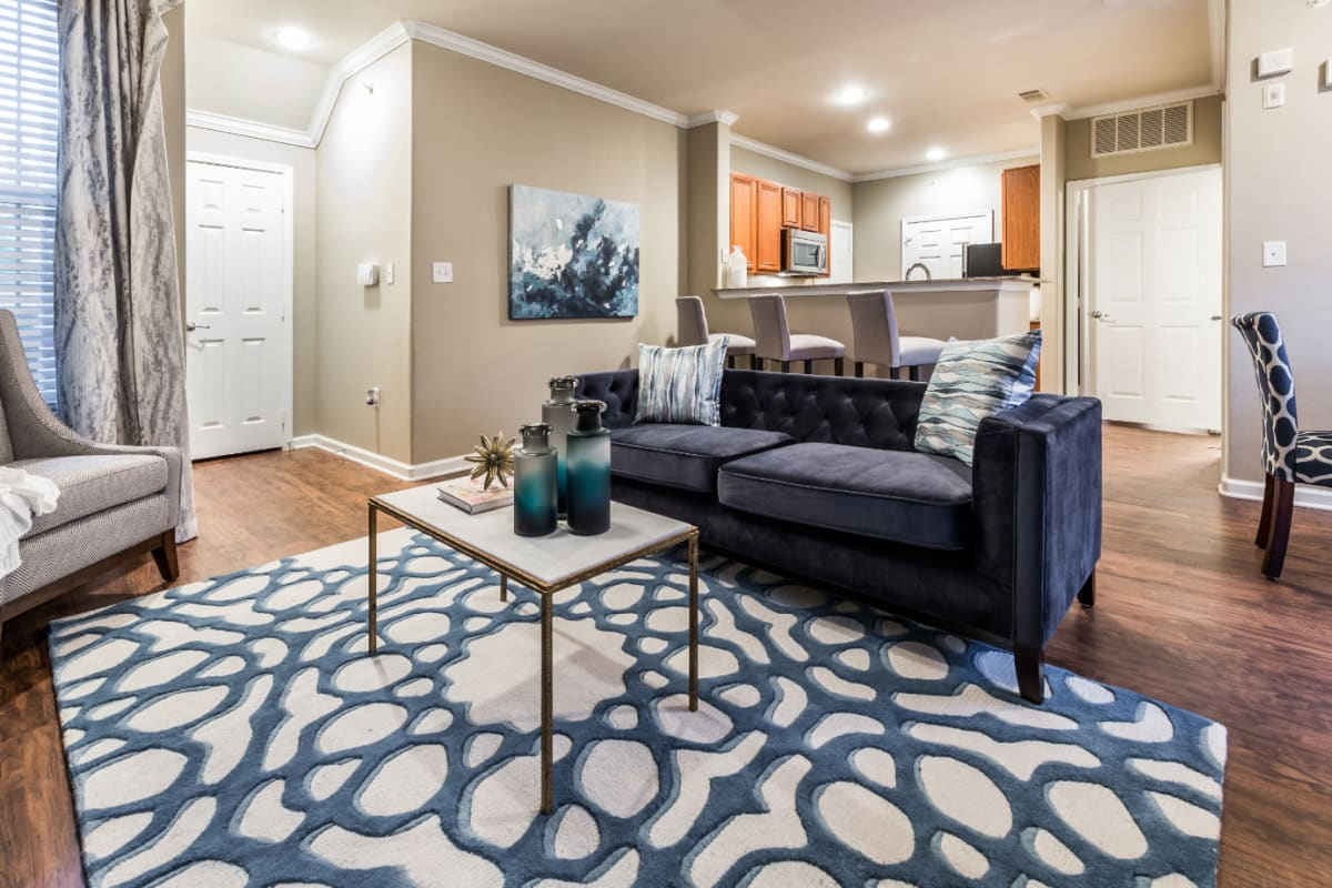 Modern style living room with full size couch, wood flooring, and sitting chair at Marquis at The Cascades in Tyler, Texas