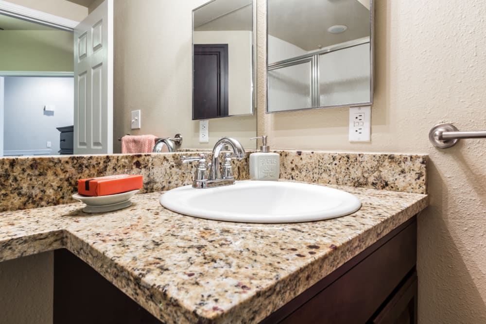 Bathroom sink with granite counter at Marquis at Stonegate in Fort Worth, Texas