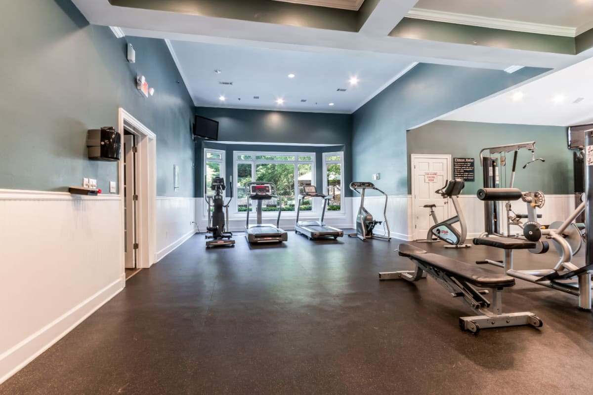 Cardio machines and weight machines in spacious fitness room overlooking pool area at Marquis at Sugarloaf in Duluth, Georgia