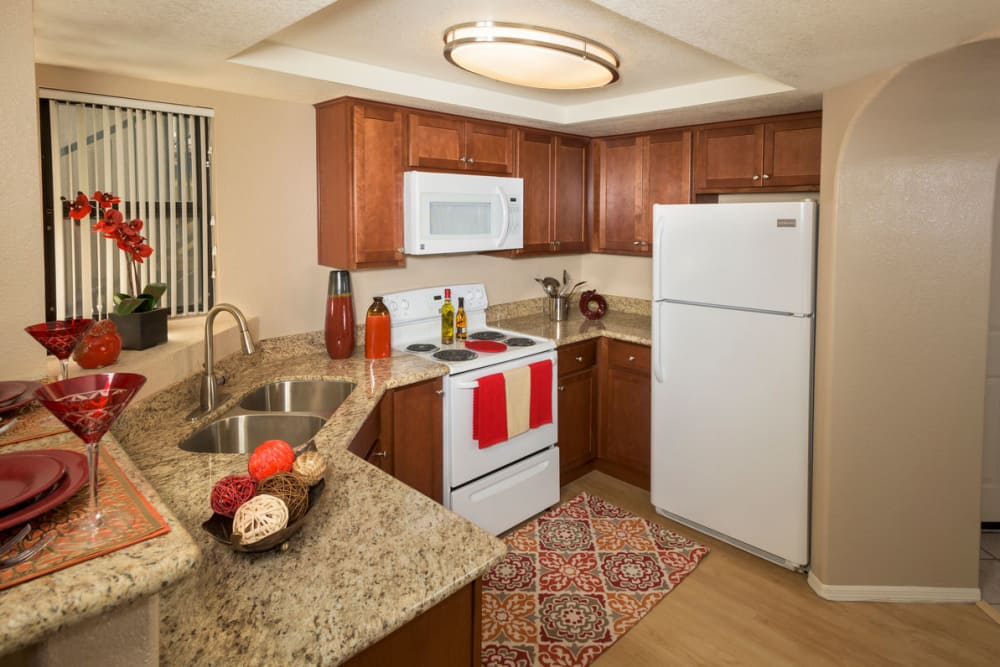 Model kitchen with ample counter space and white appliances at San Marin at the Civic Center in Scottsdale, Arizona