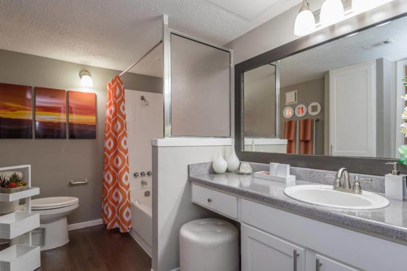 Spacious bathroom with vanity seat next to the sink at The Carling on Frankford in Carrollton, Texas