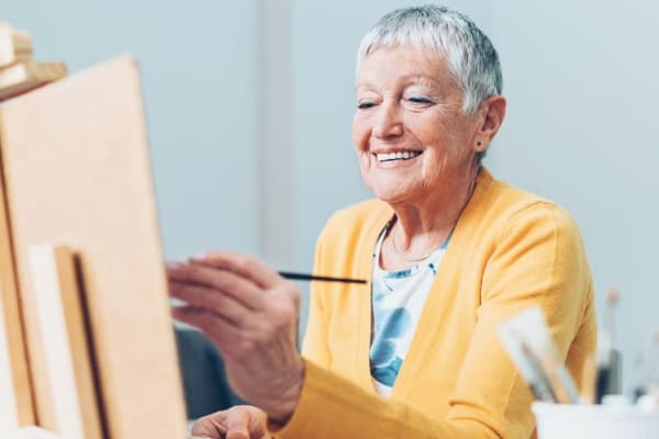 Senior woman painting at BPM Senior Living