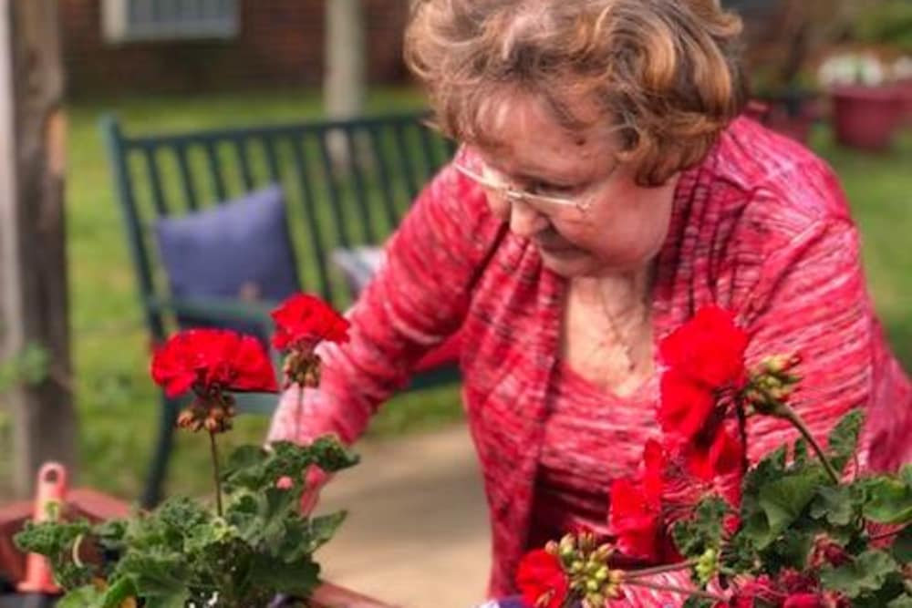 A resident planting flowers in a planter box at Autumn Woods Health Campus in New Albany, Indiana