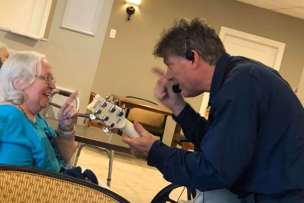 A staff member singing to a resident at Inspired Living Sun City Center in Sun City Center, Florida.