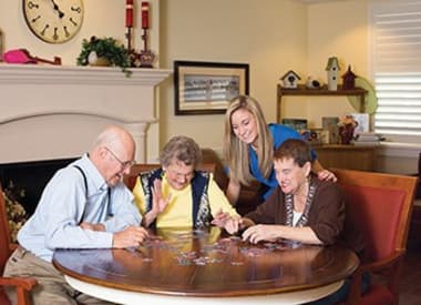 Residents working on a puzzle while caregiver looks on at Burr Ridge Senior Living in Burr Ridge, IL